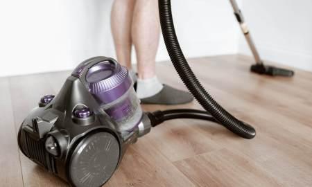man vacuuming floor during household chores
