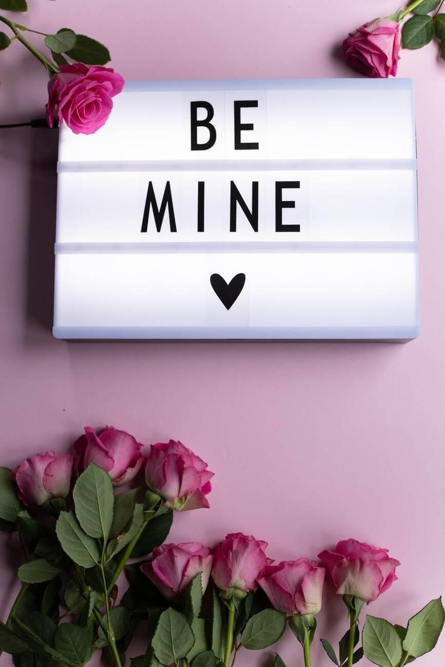 fresh roses around light box with be mine inscription