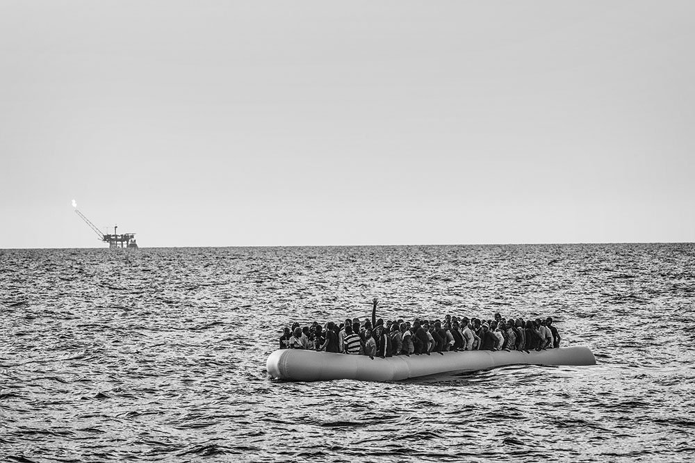 An overcrowded rubber dinghy sailed from the Libyan coast is apprached by the M.S.F. (Médecins Sans Frontières - Doctors Without Borders) search and rescue ship Bourbon Argos in the Mediterranean Sea, in international waters. The migrants on board the dinghy in distress have issued an emergency call and are waiting to be rescued. On the horizon, an offshore oil platform just off the Libyan coast. 26 August 2015. In 2015 the ever-increasing number of migrants attempting to cross the Mediterranean Sea on unseaworthy vessels towards Europe led to an unprecedented crisis. Nearly 120 thousand people have reached Italy in the first 8 months of the year. While the European governments struggled to deal with the influx, the death toll in the Mediterranean reached record numbers. Early in May the international medical relief organization Médecins Sans Frontières (M.S.F.) joined in the search and rescue operations led in the Mediterranean Sea and launched three ships at different stages: the Phoenix (run by the Migrant Offshore Aid Station), the Bourbon Argos and Dignity.