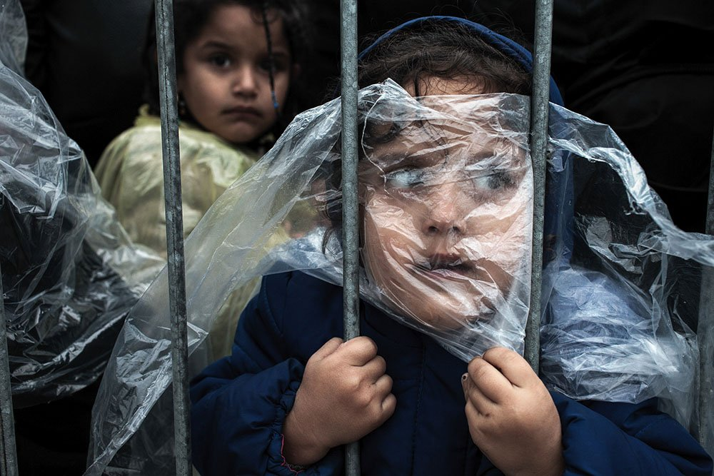 PRESEVO, SERBIA - OCTOBER 7, 2015: A child refugee is covered with raincoat while she waits in line to get registered in Presevo refugee registration camp. Most of the refugees who crossed Serbia try to continue their route towards Hungary, Croatia, Slovenia and other countries of the European Union.