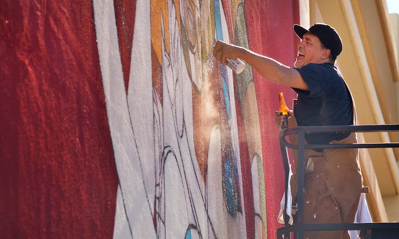 """Doze Green works on """"Tiamat"""" at the corner of 7th Street and Stewart Avenue."""