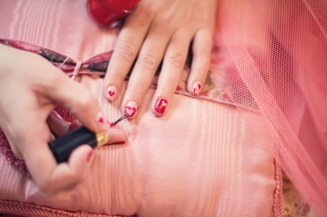 woman painting her finger nails with red heart shaped nail polish
