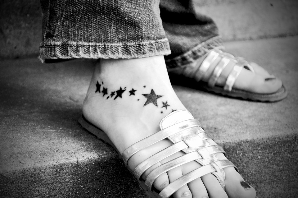 close up photo of feet with stars tattoo