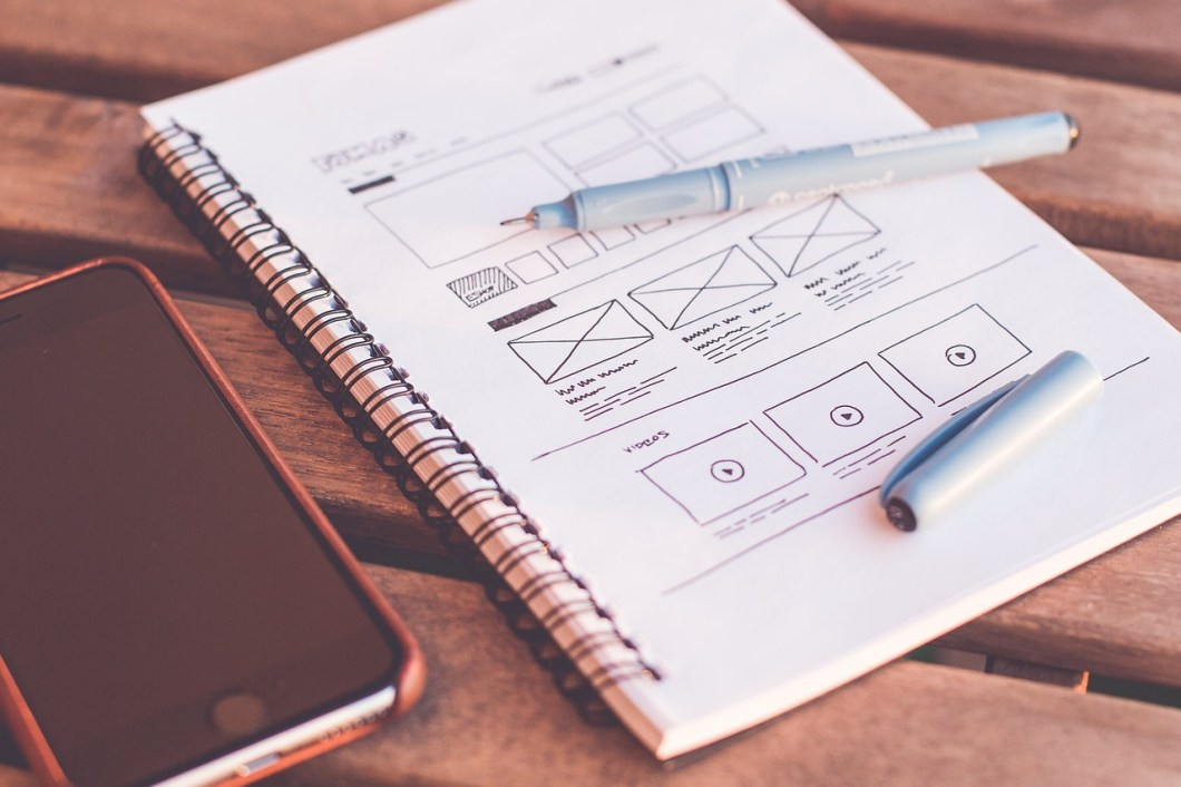 notebook with sketch web design and phone beside how to get web design clients fast