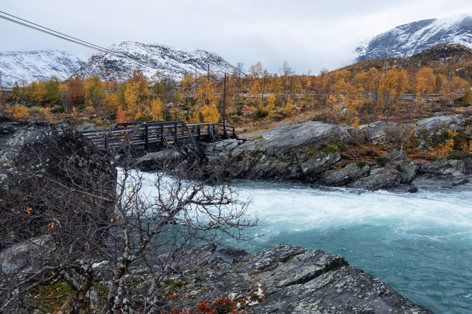 snowy mountains and blue water in a river with autumn colors around