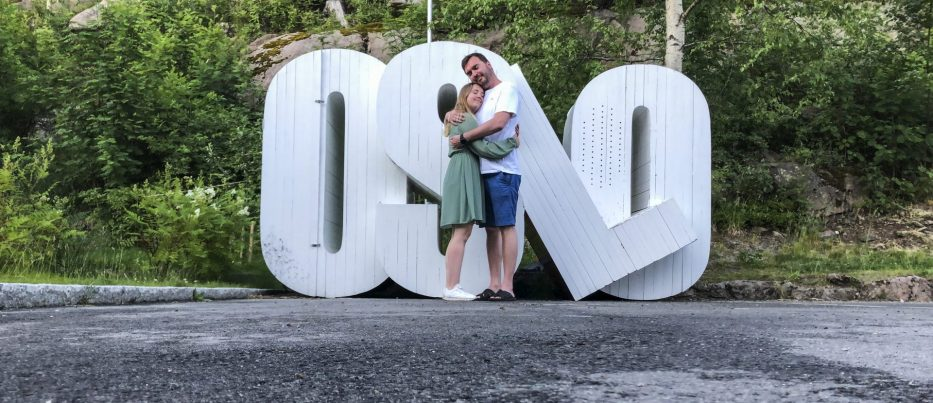 Man and woman hugging in front of installation which says OSLO