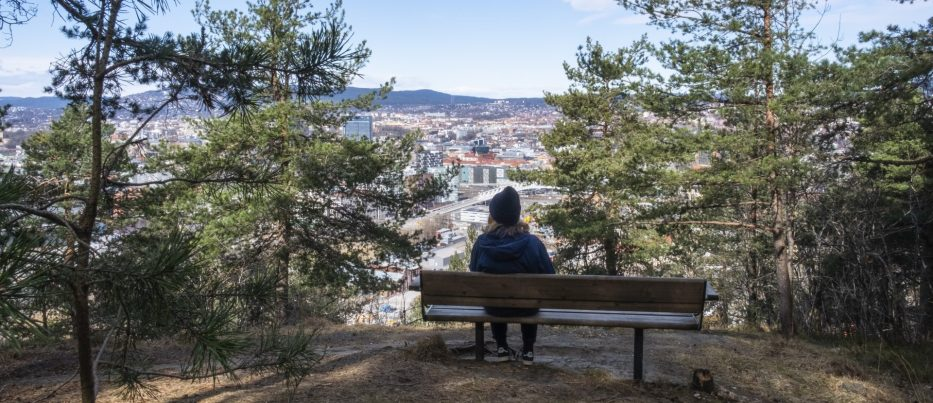 Girl sitting on bench in the forest watching Oslo skyline below