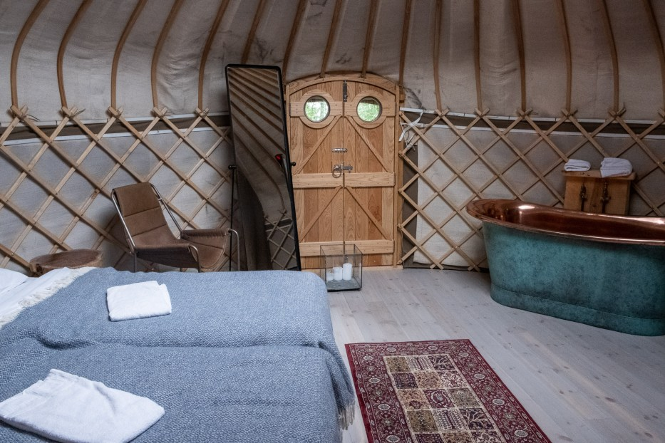 The inside of a luxury yurt at canvas hove with a huge bed, chair, mirror, door, bath tub and carpet