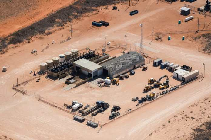 Aerial view of industrial site with rounded metal and white boxy warehouses, large tanks, and heavy equipment in the desert.