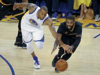 Andre Iguolada, de los Warriors, y Kyrie Irving, de los Cavaliers, van tras un balón suelto en el quinto partido de la serie final del baloncesto de la NBA.