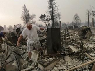 Un hombre y su hijo miran los restos de su casa destruida por los incendios en Santa Rosa, California