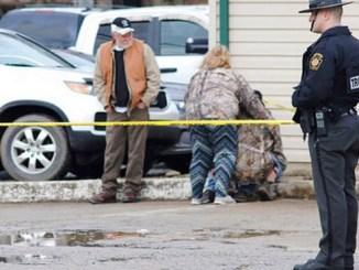 Un policía monta guardia mientras otras personas se consuelan cerca del lugar de un tiroteo en un lavado de autos de Mecrof, Pensilvania, el domingo 28 de enero de 2018