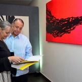"""Cassianna de Álvarez y Francisco Álvarez Alma observan el catálogo de la exposición """"Elementalismo Intuitivo"""", del artista Jennaro González Pacheco."""