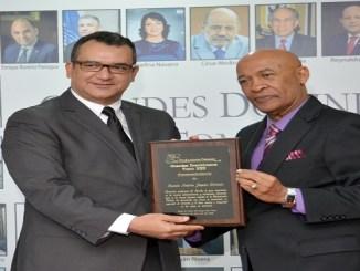 El presidente del TSE, Román Jáquez Liranzo, recibe la placa de reconocimiento de parte del autor del libro Carlos T. Martínez