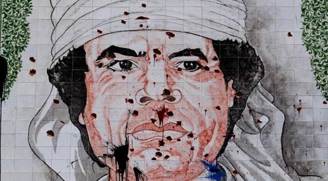Mural de Gadafi atacado por los libios despues de que el dictador huyera de Trípoli