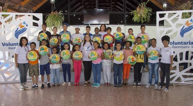 La presidenta del Voluntariado Banreservas, Jacqueline Ortiz de Lizardo, junto a hijos de empleados de la institución financiera.