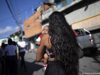 Nicol Ramírez, de 15 años, lleva a su bebé a un laboratorio donde pagará para hacerse una prueba de embarazo, requisito previo para un implante hormonal para prevenir futuros embarazos, de los cuales hay un número muy limitado, en el barrio Caucaguita de la afueras de Caracas, Venezuela.