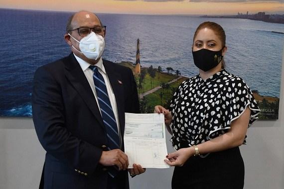 Rafael Santos Badía, director general del INFOTEP, recibe el cheque de manos de Gloria Reyes, directora de PROSOLI