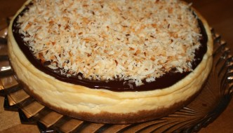 Coconut Cheesecake has a smooth coconut graham cracker crust covered with a creamy cheesecake, which is then covered with a smooth decadent chocolate layer that is finished off with crunchy toasted coconut.
