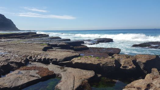 waves breaking over rocks with water pools in the foreground at Bar Beach Newcastle