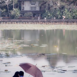 Couple under umbrella in the park