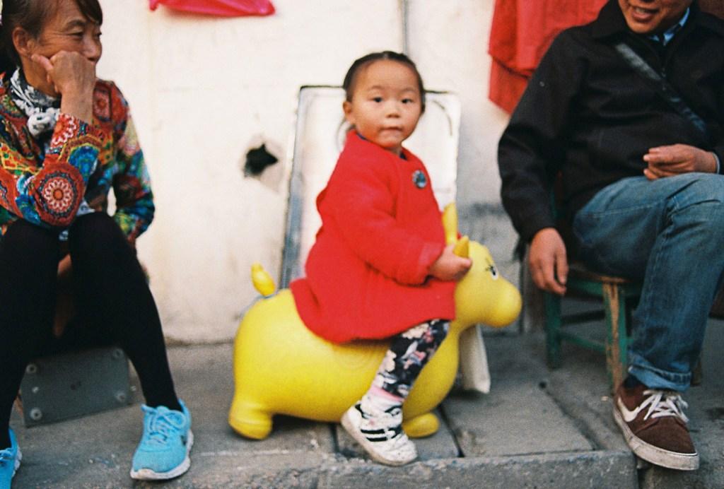 Criança brincando em cavalo amarelo
