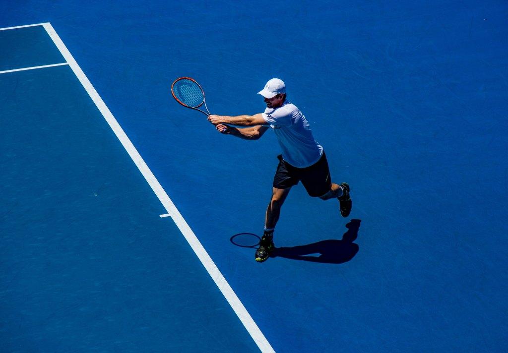 Aprenda como importar roupas esportivas Homem jogando tênis em quadra azul