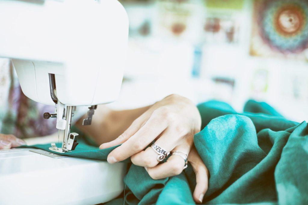 4 Dicas para Importar Tecidos da China Mulher costurando em máquina industrial