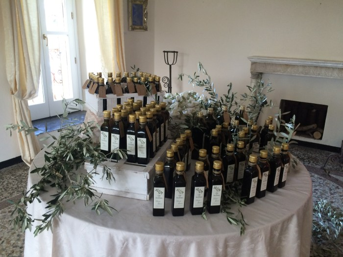 Em uma das salas, uma mesa com azeites e folhas de oliveira compunham a ornamentação da festa de casamento