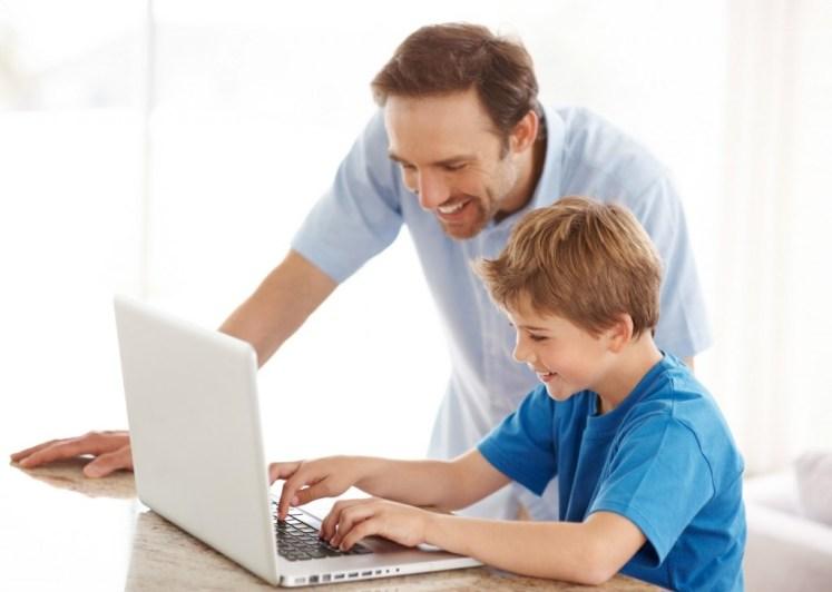 Padre acompañar al hijo a usar la computadora
