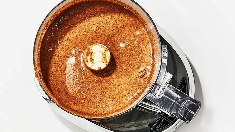 What is Nut Butter? A Natural Plant Based Alternative. Image of a food processor with hazelnut butter being made. This is a rich coffee brown colour with a slick glazed appearance to it in a modern looking food processor