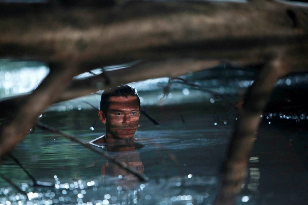 A man in water in trees in No One Lives