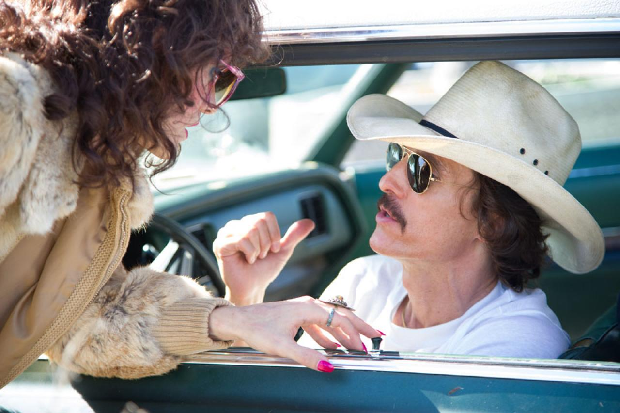 a man in a car wearing a cowboy hat talking to a woman