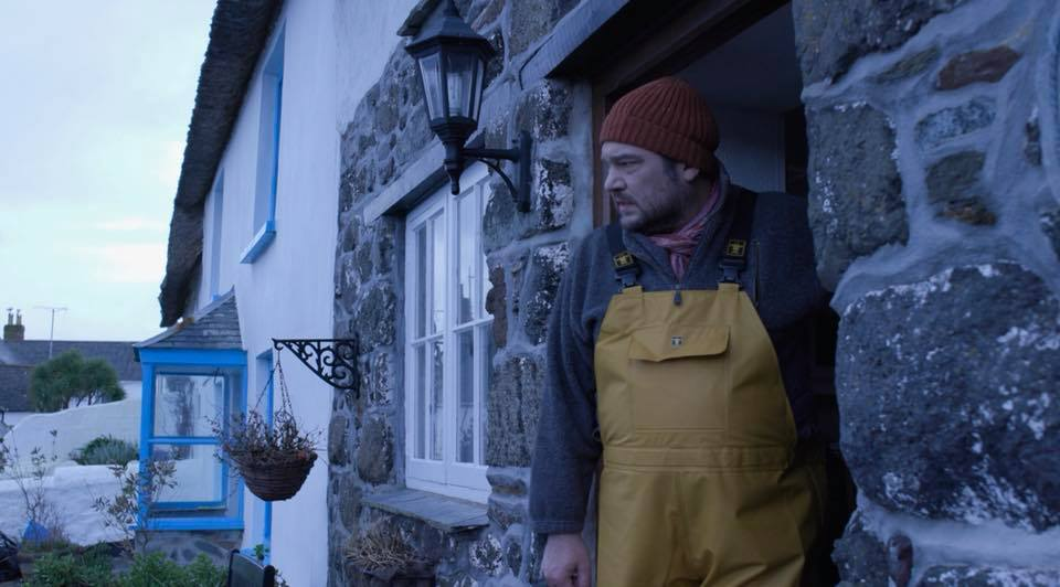 An image of a fisherman at a doorway. A still from the film Serpentine by Grace Fox