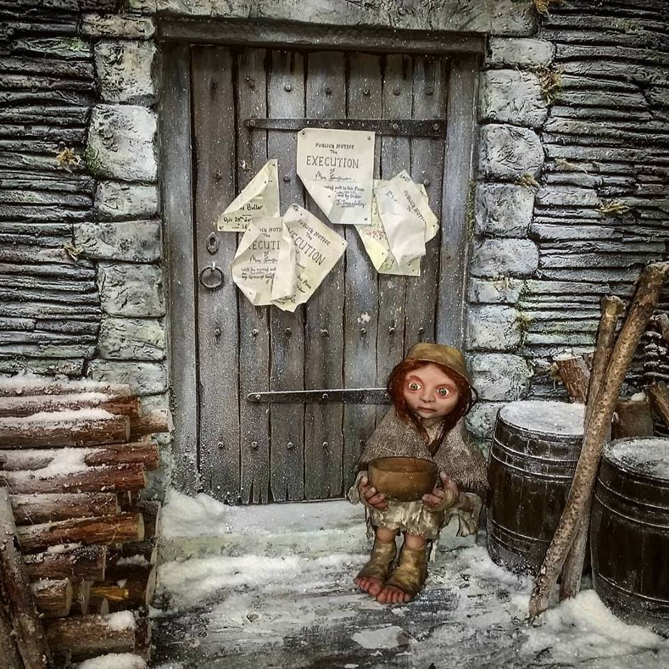 The Legend of Jan Tregeagle still:: an orphan girl puppet sits outside the courthouse in the snow with a bowl in her hands