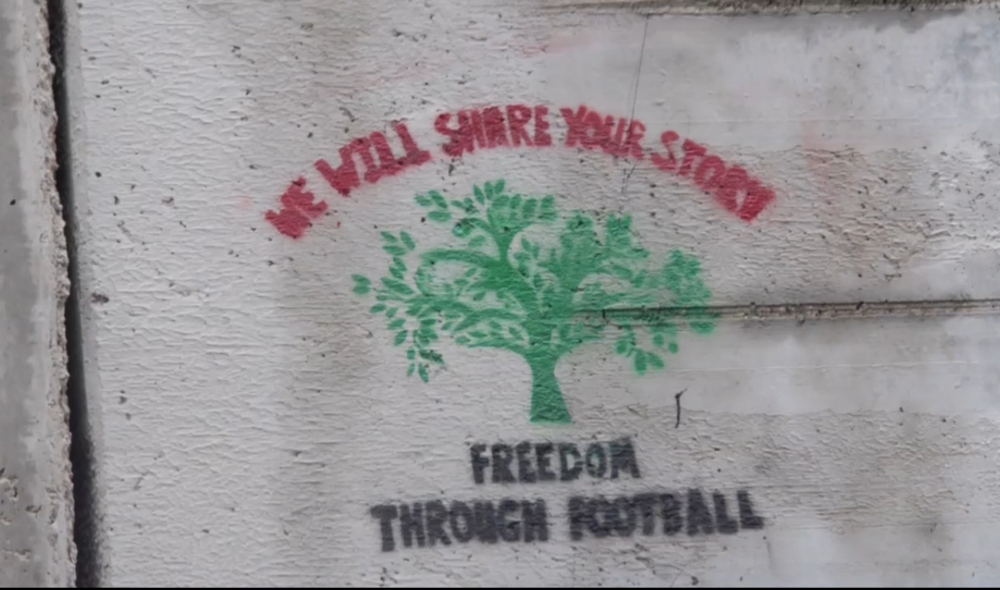 Freedom football a green tree with red and black words