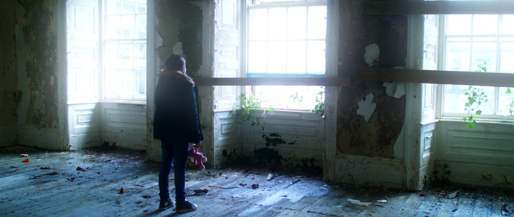 A still from Billy Abbott's Elephant video for Haunt The Woods and child looks out the window of a derelict building holding a knitted toy elephant