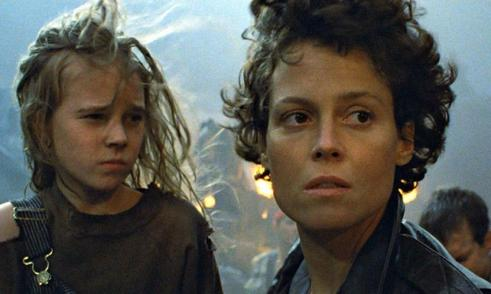 signory weaver looks out to the distance and a girl looks at her