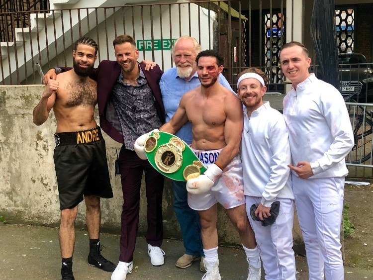 six people are in a row. There are two boxers, one is holding a belt and two people all dressed in white