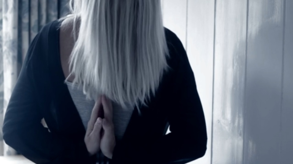 a woman holds her hands in a prayer position with her long hair over her face