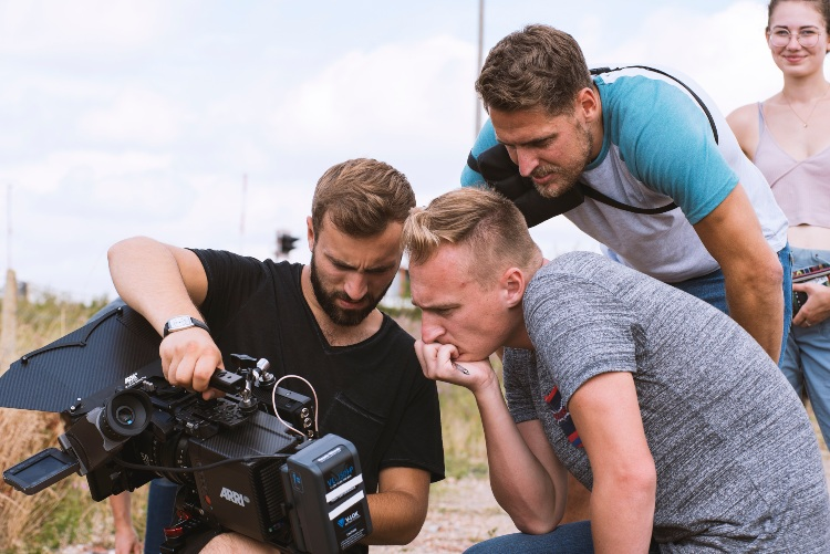 three men look at a camera; the director has his chin in his hand. In the background a woman looks at us