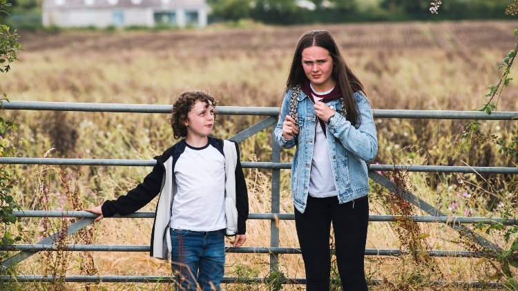 still from Safekeeping: a girl and a younger boy are facing the camera, the girl looking at us,the boy looking at the girl. There is a metal fence behind them and behind that a field of wheat