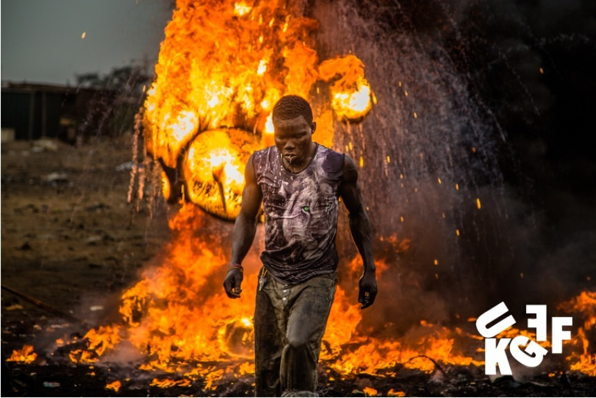 a still from Welcome to Sodom at the Green Film Festival; a man is walking away from a burning pile behind him