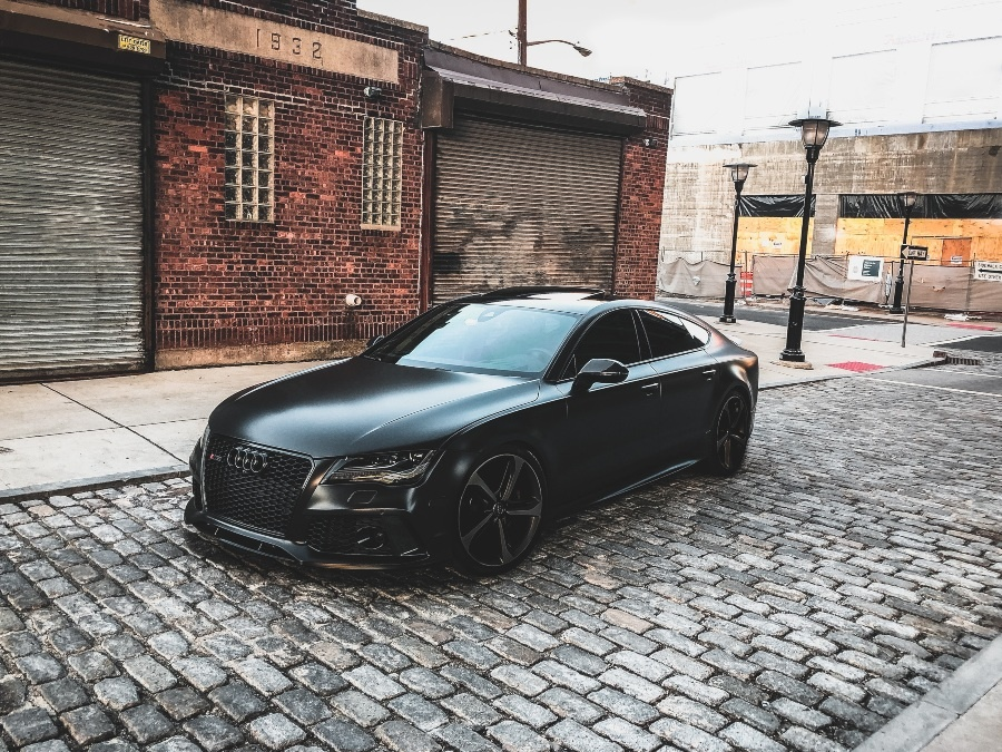 a black audi car on a cobbled road in front of stone buildings