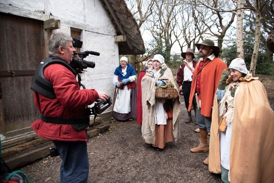 a man with a camera is talking to people in 17th century dress