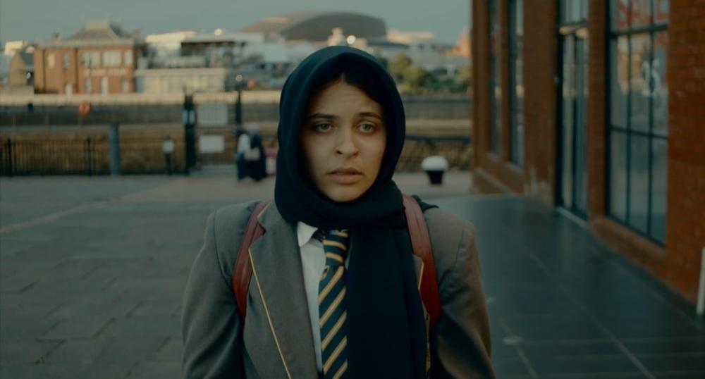 a school girl in a school uniform and wearing a head scarf is looking worried