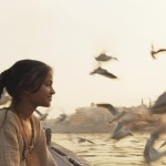 a girl is on a river in india and birds are flying around her