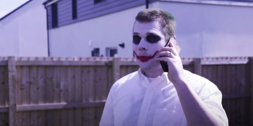 a man dressed as the joker on his phone in a garden