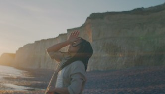 a woman on a beach with cliffs behind her
