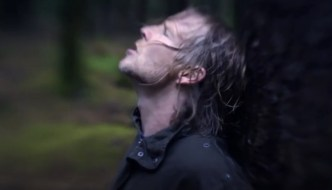 a man looks to the sky with his back to a tree. A still from Taker by Alexander Blackwood